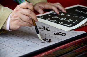 The hands of an elder person writing Chinese calligraphy